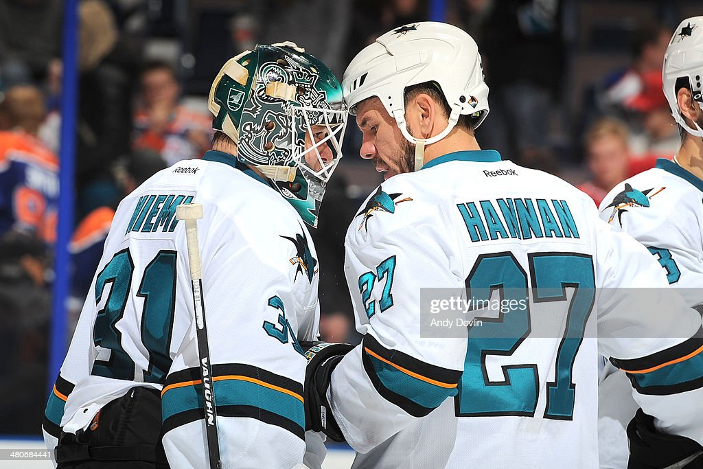 Antti Niemi #31 and Scott Hannan #27 of the San Jose Sharks celebrate after winning the game against the Edmonton Oilers on March 25, 2014 at Rexall Place in Edmonton, Alberta, Canada.