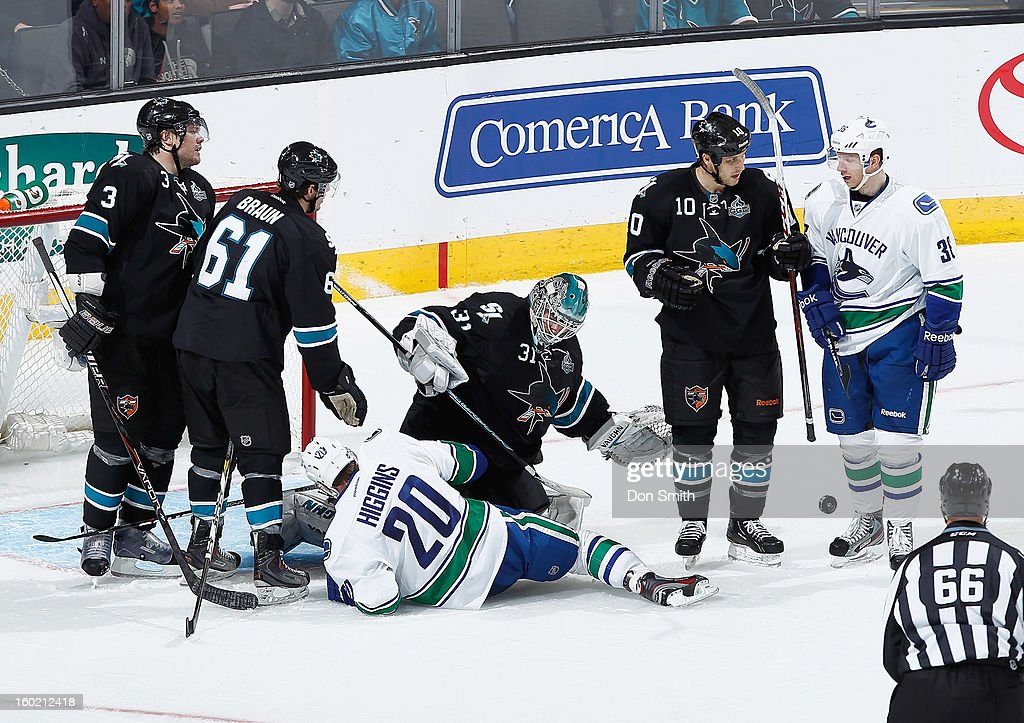 Antti Niemi #31, Andrew Desjardins #10, Justin Braun #61 and Douglas Murray #3 of the San Jose Sharks protect the net against Chris Higgins #20 and Jannik Hansen #36 of the Vancouver Canucks during an NHL game on January 27, 2013 at HP Pavilion in San Jose, California.