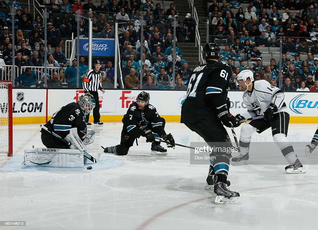 Antti Niemi #31, Brad Stuart #7 and Justin Braun #61 of the San Jose Sharks protect the net against Justin Williams #14 of the Los Angeles Kings during an NHL game on April 3, 2014 at SAP Center in San Jose, California.