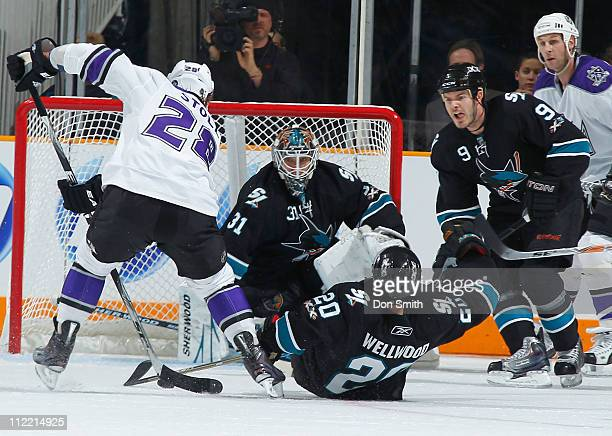 Antti Niemi, Ian White, and Kyle Wellwood of the San Jose Sharks protect the net against Jarret Stoll of the Los Angeles Kings in Game 1 of the...