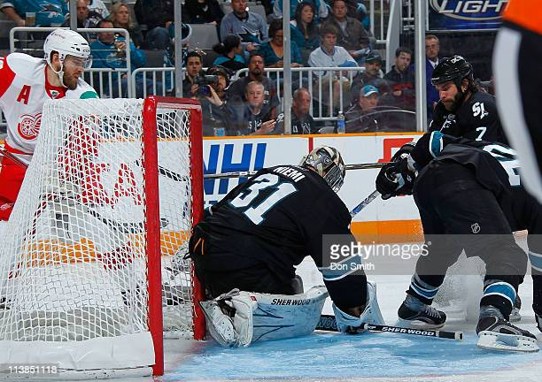 Antti Niemi, Niclas Wallin, and Dan Boyle of the San Jose Sharks defend the net against Henrik Zetterberg of the Detroit Red Wings in Game Five of...