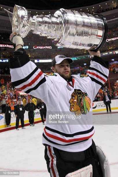 Antti Niemi of the Chicago Blackhawks hoists the Stanley Cup after teammate Patrick Kane scored the game-winning goal in overtime to defeat the...