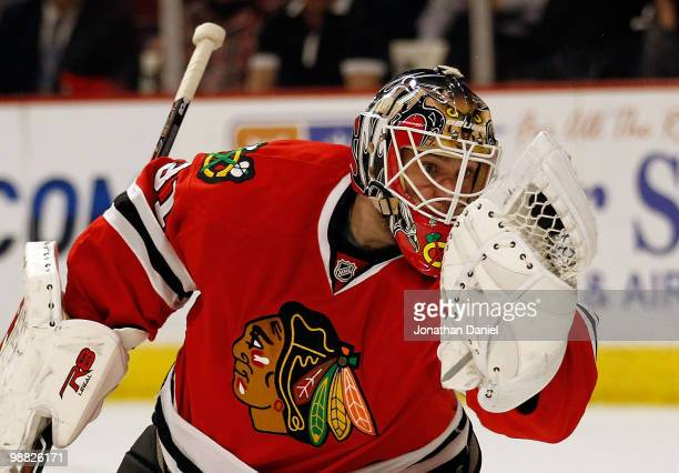Antti Niemi of the Chicago Blackhawks looks at the puck in his glove after a save against the Vancouver Canucks in Game Two of the Western Conference...