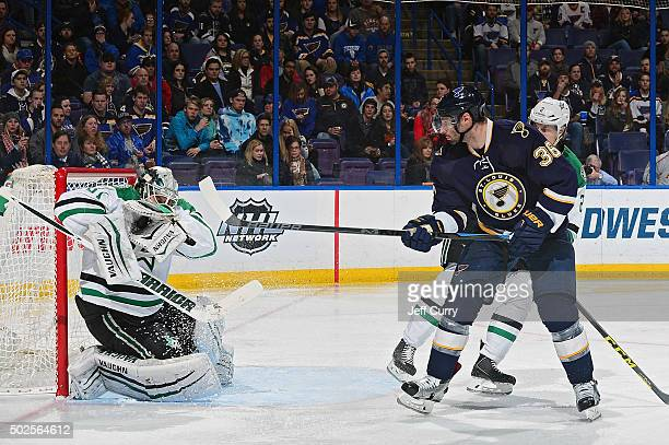 Antti Niemi of the Dallas Stars makes a glove save as Troy Brouwer of the St Louis Blues looks for a rebound on December 26 2015 at Scottrade Center...
