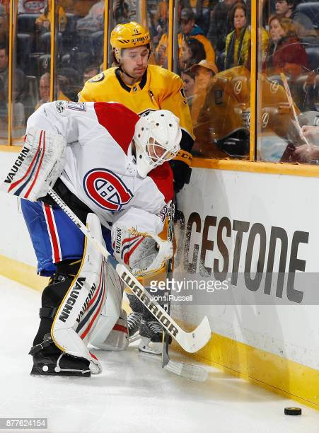 Antti Niemi of the Montreal Canadiens battles behind the net for the puck against Filip Forsberg of the Nashville Predators during an NHL game at...