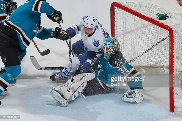 Antti Niemi of the San Jose Sharks looks for the puck against Mikhail Grabovski of the Toronto Maple Leafs during an NHL game on January 11, 2011 at...
