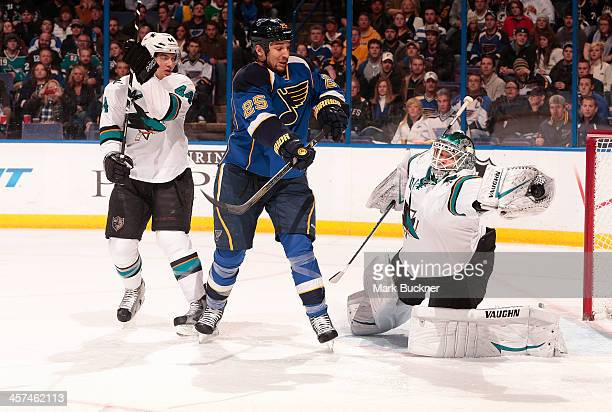 Antti Niemi of the San Jose Sharks makes a glove save as Chris Stewart of the St Louis Blues looks for a rebound during an NHL game on December 17...