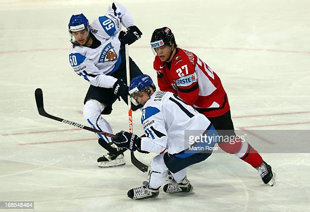 Antti Pihlstrom of Finland and Thomas Hundertpfund of Austria battle for the puck during the IIHF World Championship group H match between Finland...