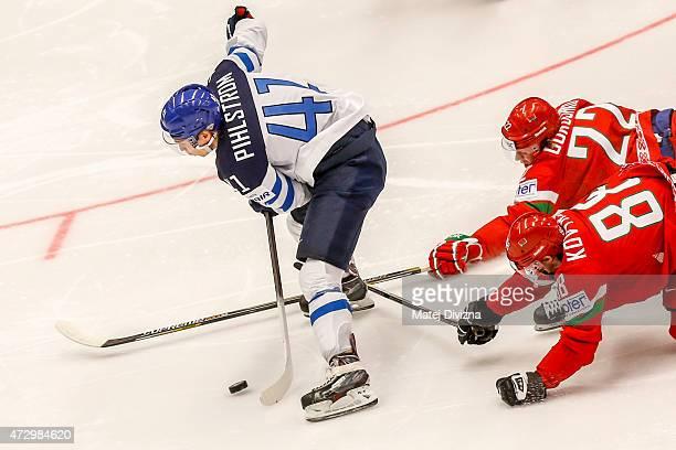 Antti Pihlstrom of Finland and Yevgeni Kovyrshin and Oleg Goroshko of Belarus battle for the puck during the IIHF World Championship group B match...