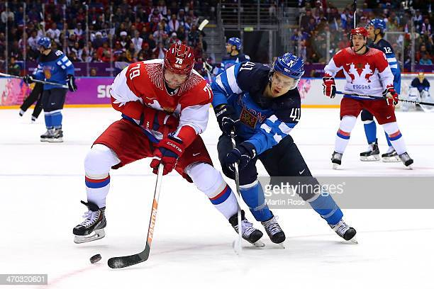 Antti Pihlstrom of Finland challenges Andrej Markov of Russia for the puck during the Men's Ice Hockey Quarterfinal Playoff on Day 12 of the 2014...