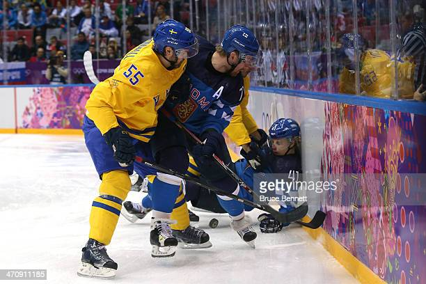 Antti Pihlstrom of Finland falls to the ice as Niklas Kronwall of Sweden and Leo Komarov of Finland compete for the puck during the Men's Ice Hockey...