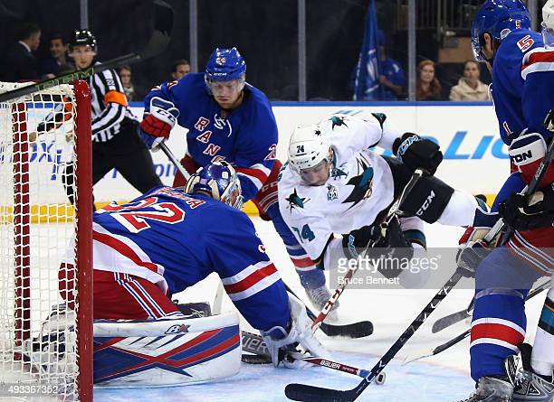 Antti Raanta and Oscar Lindberg of the New York Rangers defend against Dylan DeMelo of the San Jose Sharks during the first period at Madison Square...