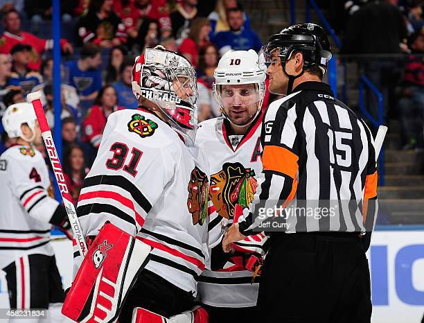 Antti Raanta and Patrick Sharp of the Chicago Blackhawks talk with referee Stephane Auger on October 25 2014 at Scottrade Center in St Louis Missouri