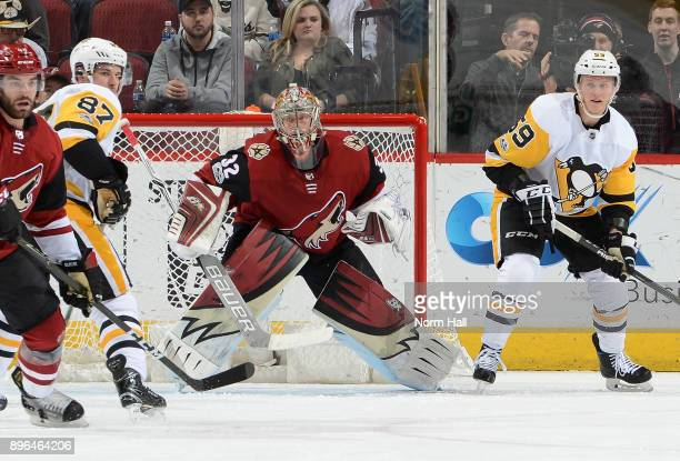 Antti Raanta of the Arizona Coyotes gets ready to make a save between Sidney Crosby and Jake Guentzel of the Pittsburgh Penguins at Gila River Arena...