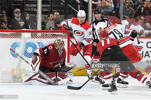Antti Raanta of the Arizona Coyotes gets ready to make a save on a shot by Micheal Ferland of the Carolina Hurricanes as Andrei Svechnikov looks for...