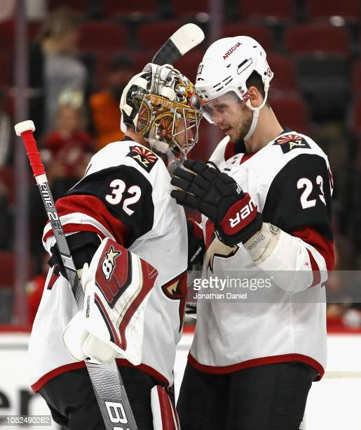 Antti Raanta of the Arizona Coyotes is congratulated by Oliver EkmanLarsson after a win over the Chicago Blackhawks at the United Center on October18...