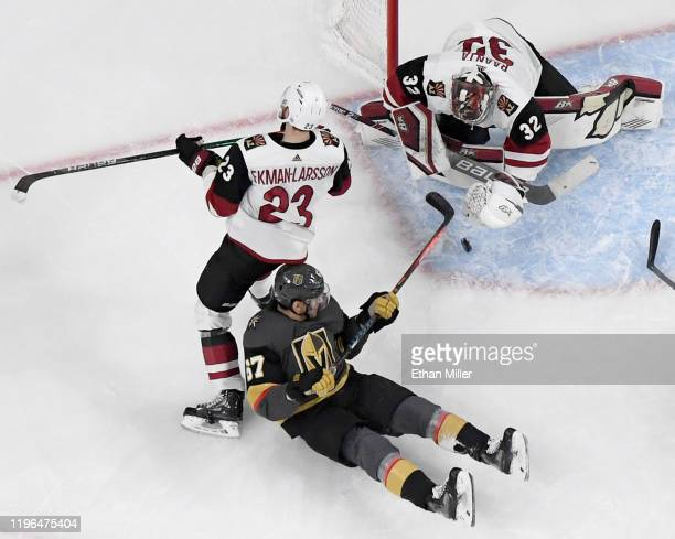Antti Raanta of the Arizona Coyotes makes a save against Max Pacioretty of the Vegas Golden Knights as Oliver EkmanLarsson of the Coyotes defends in...