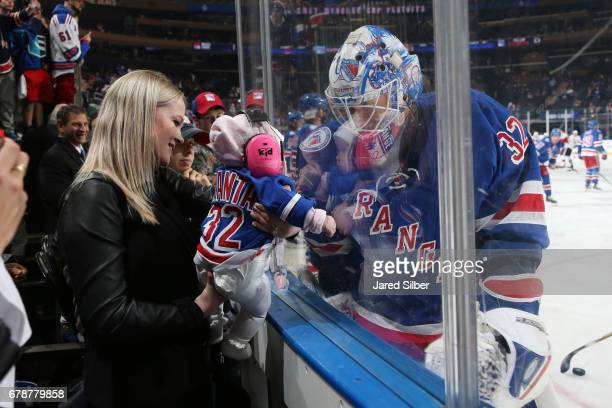 Antti Raanta of the New York Rangers greets his daughter and wife along the boards during pregame warmups before the game against the Ottawa Senators...