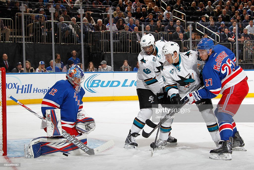 Antti Raanta #32 of the New York Rangers makes a save as Ryan McDonagh #27 battles against Tommy Wingels #57 and Joel Ward #42 of the San Jose Sharks in front of the net at Madison Square Garden on October 19, 2015 in New York City.