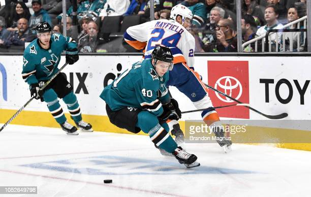 Antti Suomela of the San Jose Sharks battles for the puck against Scott Mayfield of the New York Islanders at SAP Center on October 20 2018 in San...