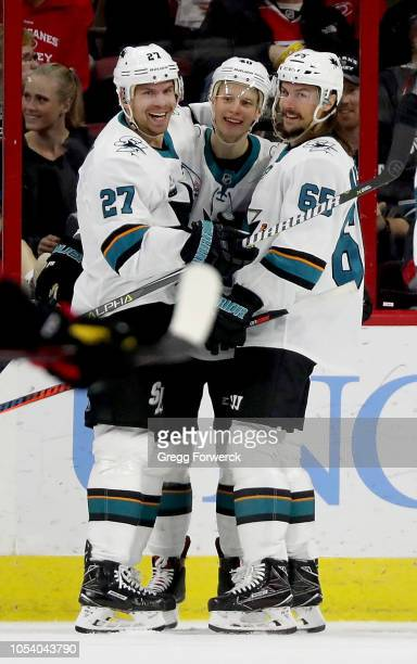 Antti Suomela of the San Jose Sharks celebrates with teammates Joonas Donskoi and Erik Karlsson after scoring his first NHL goal during a game...