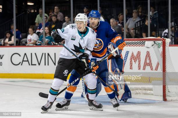 Antti Suomela of the San Jose Sharks fights for position in front of New York Islanders Johnny Boychuk and Robin Lehner during the game between the...