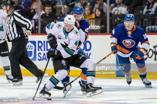 Antti Suomela of the San Jose Sharks protects the puck against New York Islanders Center Brock Nelson during the game between the New York Islanders...