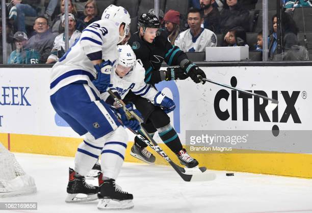 Antti Suomela of the San Jose Sharks skates after the puck with Morgan Rielly and Travis Dermott of the Toronto Maple Leafs at SAP Center on November...