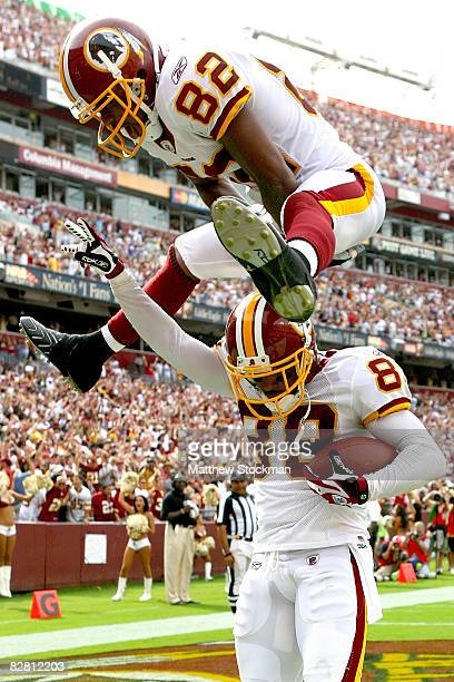 Antwaan Randle El of the Washington Redskins leaps over Santana Moss after Moss scored the go ahead touchdown in the fourth quarter against the New...