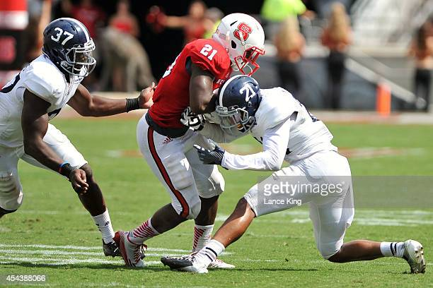 Antwione Williams and Nick Wright of the Georgia Southern Eagles tackle Matt Dayes of the North Carolina State Wolfpack at Carter-Finley Stadium on...