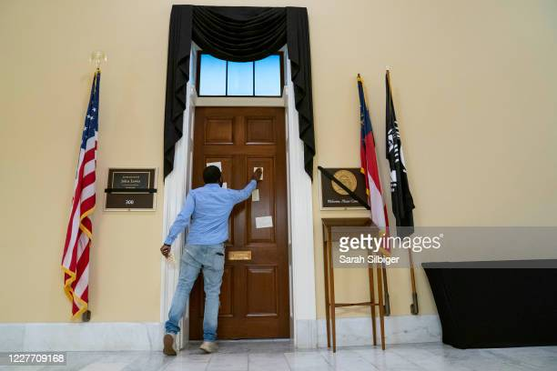 Antwoin Monach, a staff member for Rep. Hank Johnson , places a note on the office door of civil rights activist Rep. John Lewis , who died last...
