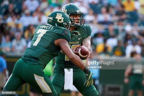 Anu Solomon of the Baylor Bears hands the ball off to John Lovett against the Liberty Flames during a football game at McLane Stadium on September 2,...