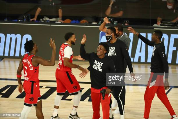 Anunoby and Norman Powell of the Toronto Raptors and the bench react during a time out against the Brooklyn Nets in the second half in game four of...