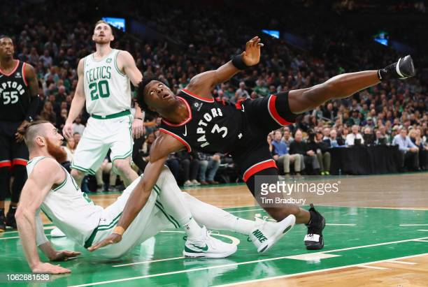 Anunoby of the Toronto Raptors falls as he shoots the ball against Aron Baynes of the Boston Celtics during the first half at TD Garden on November...