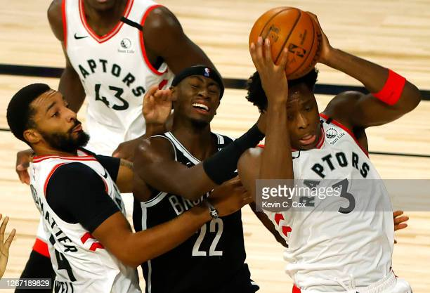 Anunoby of the Toronto Raptors grabs a rebound as Caris LeVert of the Brooklyn Nets draws a foul Norman Powell of the Toronto Raptors of the Toronto...