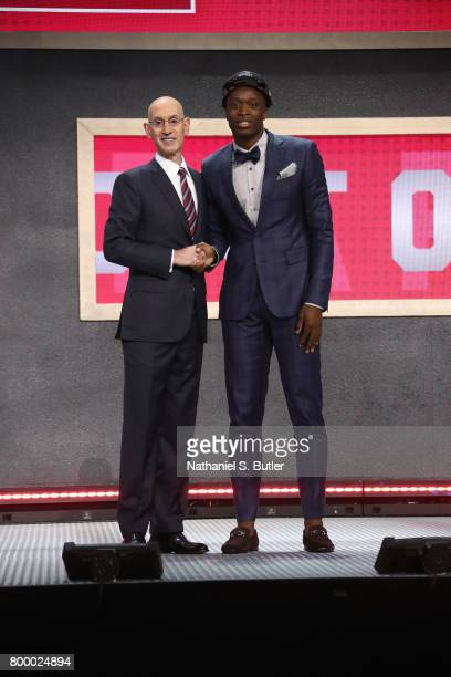 Anunoby shakes hands with NBA Commissioner Adam Silver after being selected twenty third overall by the Toronto Raptors during the 2017 NBA Draft on...