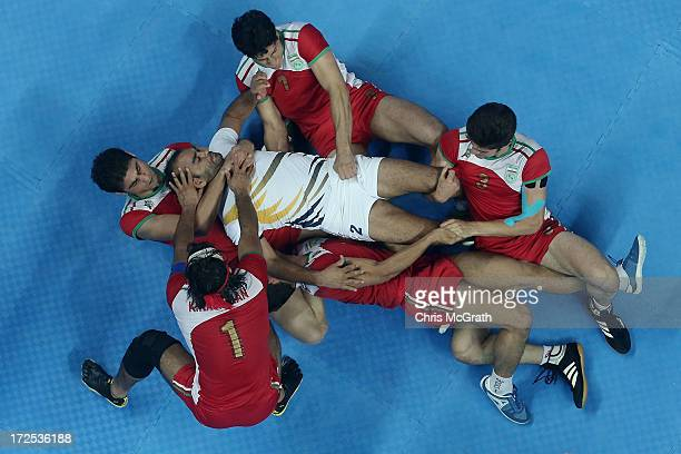 Anup Kumar of Independent Olympic Athletes is tackled by the Iran defence during the Men's Kabaddi Gold Medal match at Ansan Sangnoksu Gym on day...