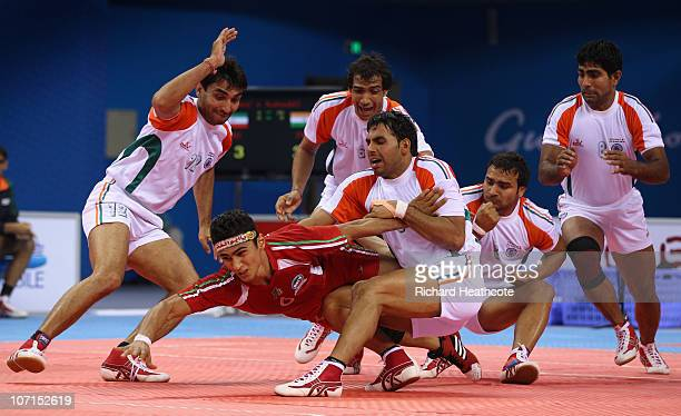 Anup Kumar of India captures Meisam Abbasi of Iran as he tries to raid for points during the Men's Kabaddi final at Nansha Gymnasium during day...