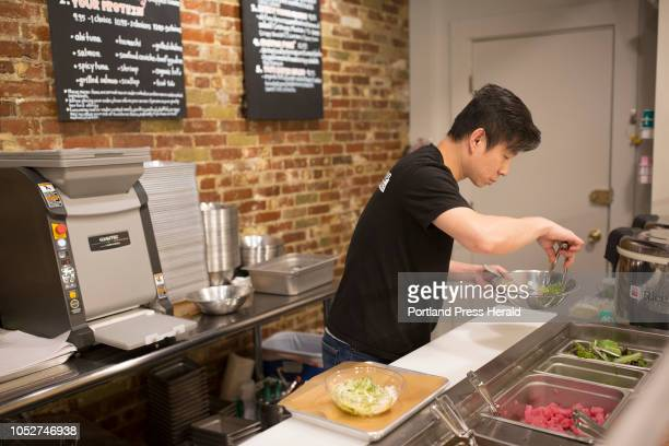 Anusat Limsitong makes a Chirashi poke bowl behind the counter of his restaurant Poke Pop in Portland on Wednesday October 17 2018 Limsitong opened...