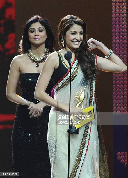 Anushka Sharma accepts the trophy for Best Leading Role Female from Shilpa Shetty during the 2011 International Indian Film Academy awards in Toronto...