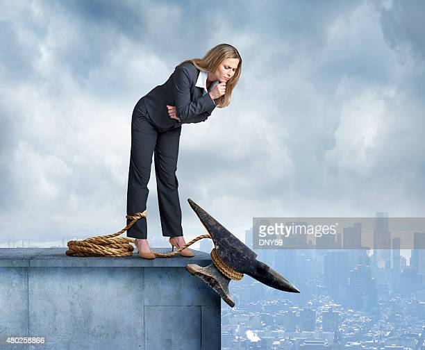 Anvil Tied Around Leg Of Businesswoman