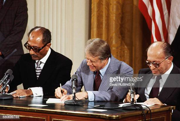 Anwar Al Sadat Jimmy Carter and Menachem Begin sign the Camp David Accord in the East Room of the White House