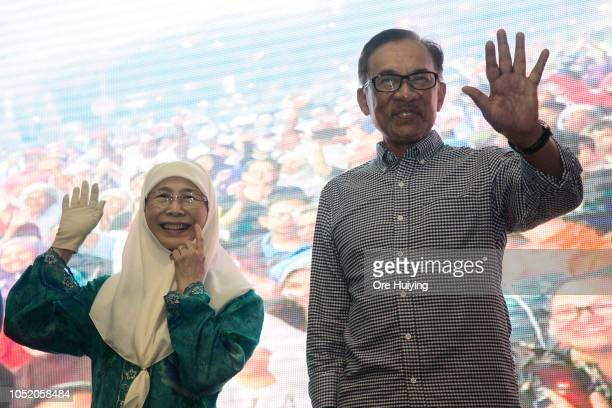 Anwar Ibrahim and his wife Wan Azizah PKR president and Malaysia's Deputy Prime Minister wave to his supporters outside the party's headquarters...