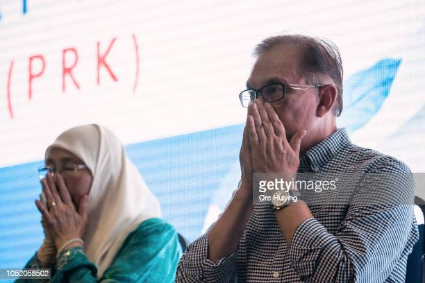 Anwar Ibrahim and his wife Wan Azizah PKR president and Malaysia's Deputy Prime Minister say their prayer outside the party's headquarters after he...