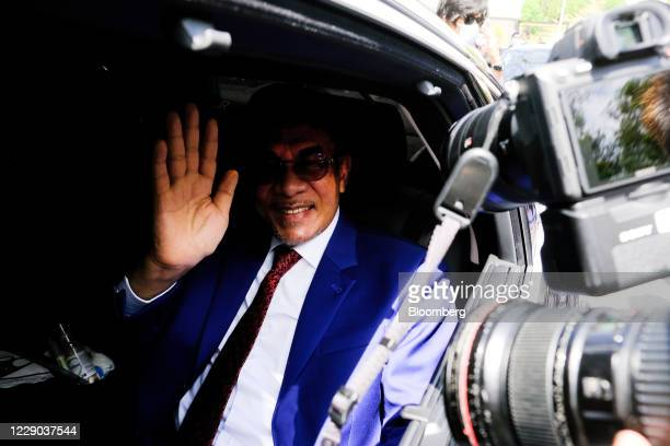 Anwar Ibrahim founder and president of the People's Justice Party waves from a vehicle as he leaves the Istana Negara palace in Kuala Lumpur Malaysia...