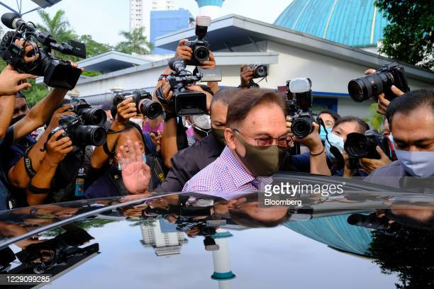 Anwar Ibrahim founder and president of the People's Justice Party enters a vehicle after speaking during a news conference outside the Bukit Aman...