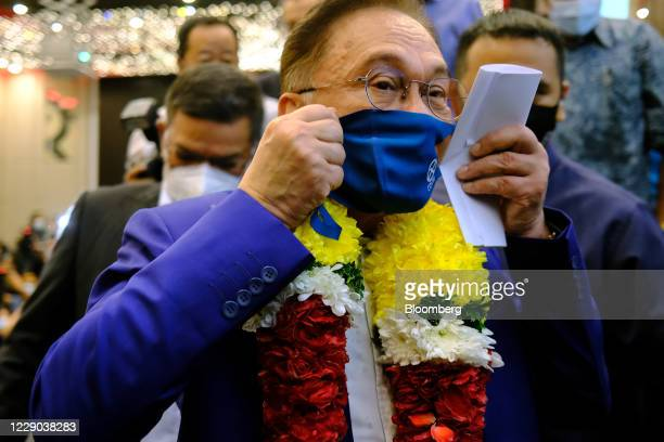 Anwar Ibrahim founder and president of the People's Justice Party puts on a protective face mask during a news conference in Kuala Lumpur Malaysia on...