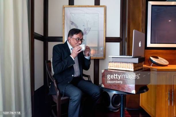 Anwar Ibrahim founder of Malaysia's People's Justice Party drinks a cup of coffee during a livestreaming interview in Hong Kong China on Wednesday...