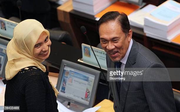 Anwar Ibrahim leader of the opposition right reacts as his daughter Nurul Izzah looks on in parliament in Kuala Lumpur Malaysia on Friday Oct 7 2011...