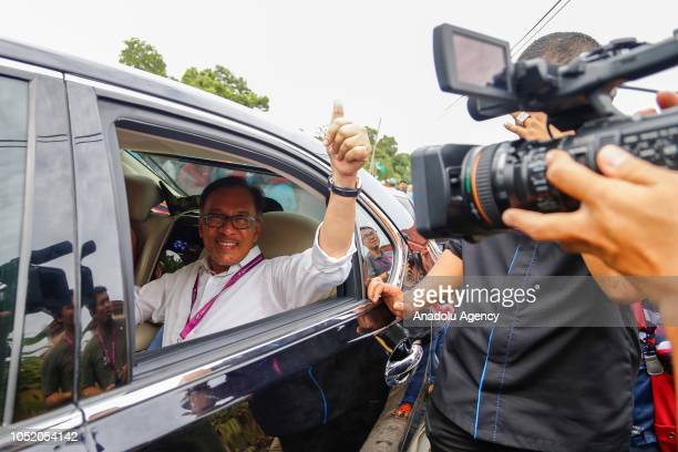 Anwar Ibrahim leader of the Pakatan Harapan Coalition greets supporters as he leaves the polling station on October 13 2018 in Port Dickson Malaysia...